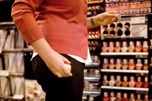 A female in the act of shoplifting or stealing puts an item under her clothes. Steve Lovegrove / Fotolia / 2157445